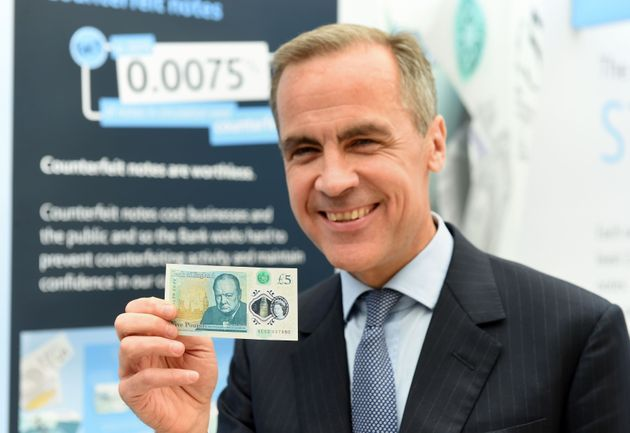 Governor of the Bank of England Mark Carney with thenew polymer £5 note featuring Sir Winston