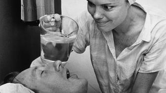8th February 1967:  Denise Strenglein of St Petersburg, Florida tries dripping water into her husband Harry's mouth to stop him snoring.  (Photo by Alan Band/Keystone Features/Getty Images)