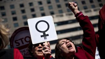 TOPSHOT - Activists protest the Trump administration and rally for women's rights during a march to honor International Woman's Day on March 8, 2017 in Washington, DC. / AFP PHOTO / Brendan Smialowski        (Photo credit should read BRENDAN SMIALOWSKI/AFP/Getty Images)
