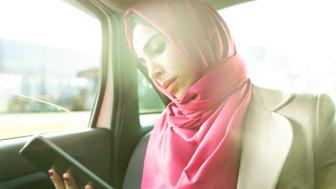 Businesswoman in a taxi using tablet. She wears headscarf.