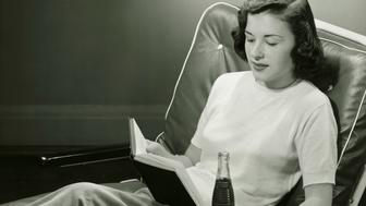 Woman with bottle of beverage, reading book, (B&W),