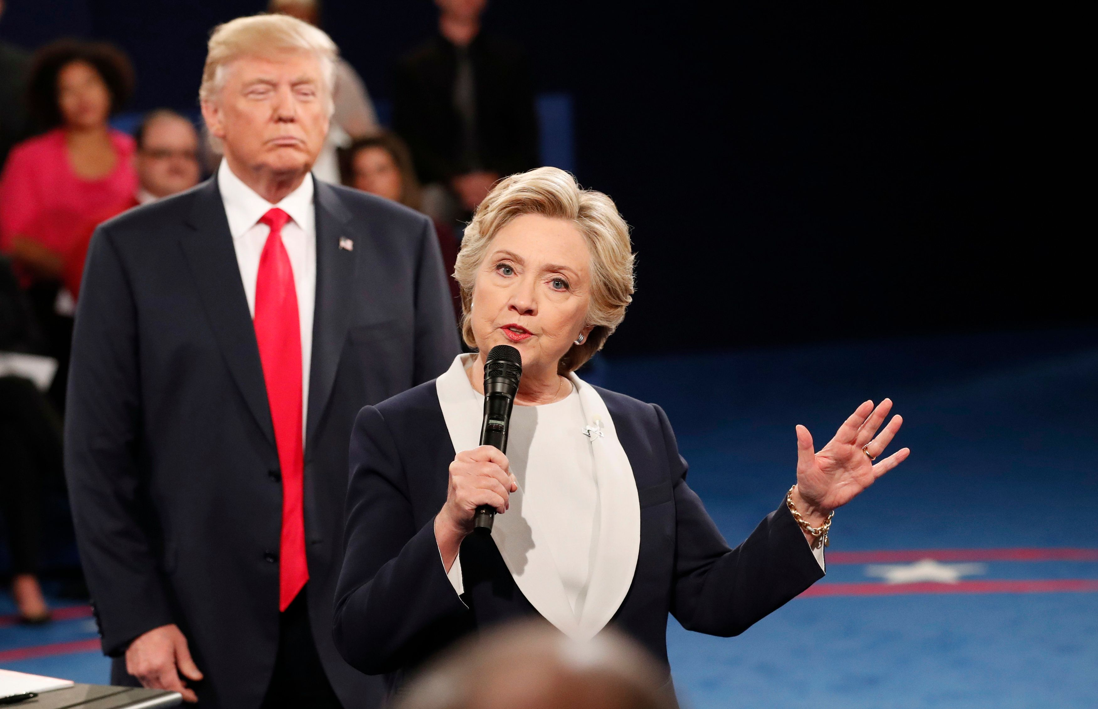 Republican U.S. presidential nominee Donald Trump listnes as Democratic nominee Hillary Clinton answers a question from the audience during their presidential town hall debate at Washington University in St. Louis, Missouri, U.S., October 9, 2016. REUTERS/Rick Wilking