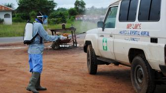 A health worker sprays disinfectant on an ambulance in Nedowein, Liberia, July 15, 2015. A Liberian woman has died of Ebola in a hospital in Monrovia shortly after being admitted, becoming the sixth confirmed case and second death since the virus resurfaced last month, a senior medical official said on Tuesday. REUTERS/James Giahyue