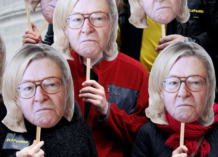 Activists wear masks of Jean-Marie Le Pen, founder of the National Front, with his daughter's hair, Marine, currently the ext