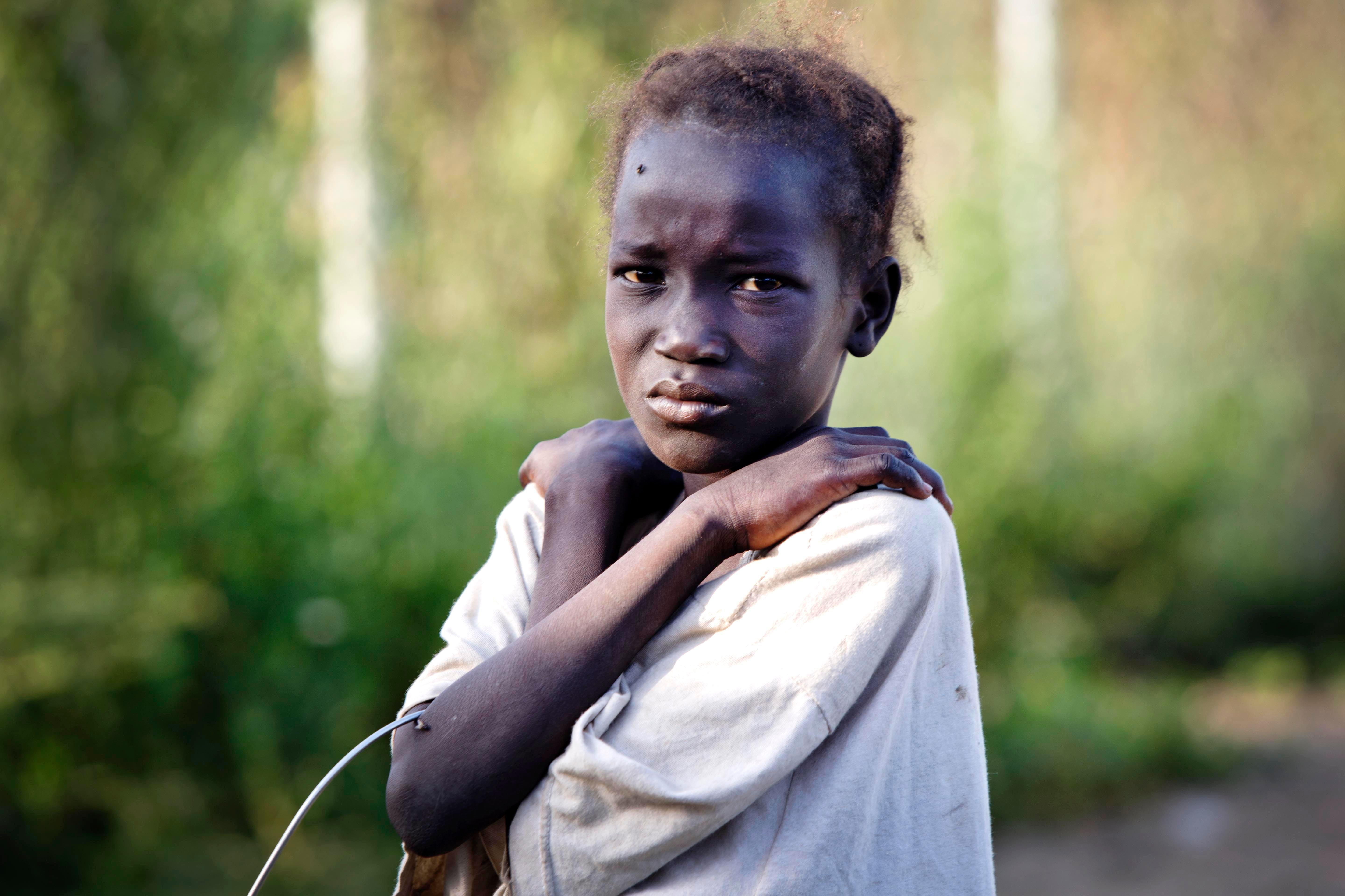 On 22 October 2016, a young girl, who has just arrived from Leer, where there is heavy fighting, poses for a photograph at the gate of  the  UN Protection of Civilian Camp (POC) Bentiu, South Sudan. Recent fighting  in Leer between Governemnt forces and rebel groups have forced thousands more people into the UN camp in Bentiu that is now home to 105,000 people.