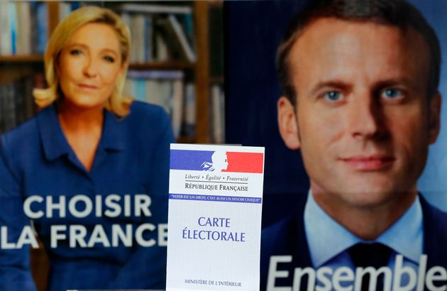 AFrench voter registration card is seen in front of official campaign posters of candidates in...