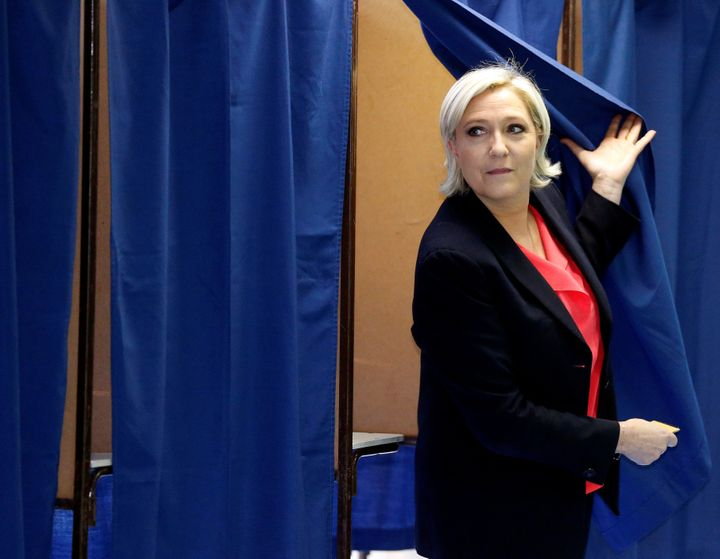 Le Pen exits a voting booth after casting her ballot.
