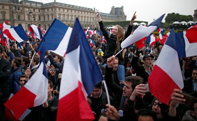 Supporters of Emmanuel Macron celebrate near the Louvre museum after results were announced in the second...