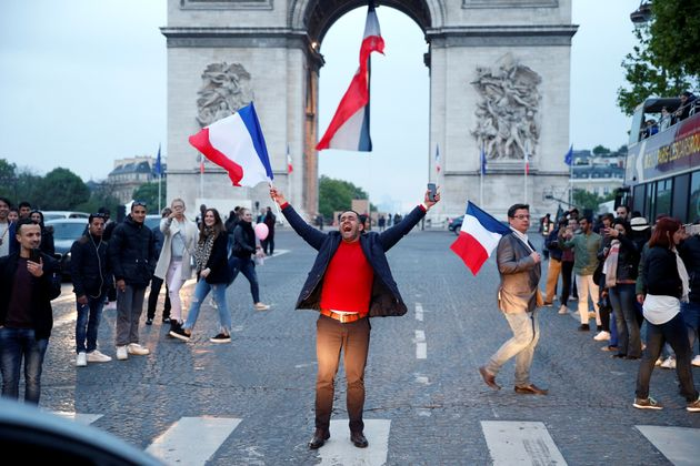 A man shouts as he waves a French national flag on the French avenue of the Champs Elysees by the Arc...