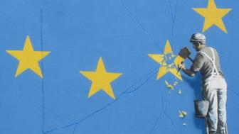 A Banksy mural showing a man chipping away at the EUs flag is seen in England