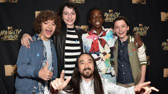 LOS ANGELES, CA - MAY 07:  (Back, L-R) Actors Gaten Matarazzo, Finn Wolfhard, Caleb McLaughlin, Noah Schnapp and (front) DJ Steve Aoki attend the 2017 MTV Movie And TV Awards at The Shrine Auditorium on May 7, 2017 in Los Angeles, California.  (Photo by Kevin Mazur/WireImage)