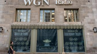 A woman walks past a WGN Radio window display on the side of Tribune Tower in Chicago, Illinois, U.S., on Friday, Aug. 7, 2015. Tribune Media Co. is scheduled to report second-quarter earnings results before the opening of U.S. financial markets on August 13. Photographer: Christopher Dilts/Bloomberg via Getty Images