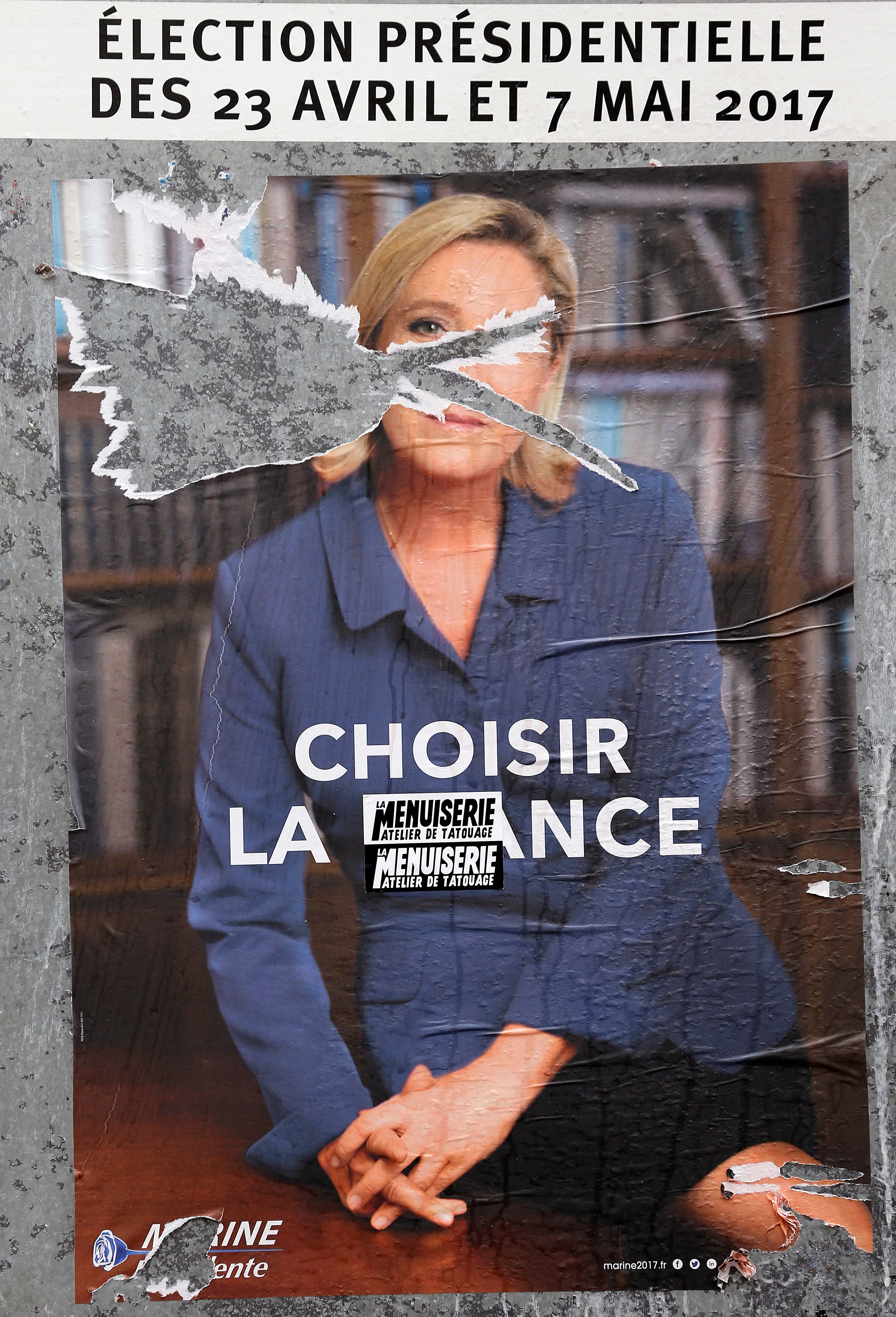 PARIS, FRANCE - MAY 04:  A damaged official campaign poster of Marine Le Pen, French National Front (FN) political party leader is displayed on May 04, 2017 in Paris, France. Le Pen and Macron arrived in the lead positions in the first round of the presidential elections. France will hold the second round on May 07, 2017.  (Photo by Chesnot/Getty Images)