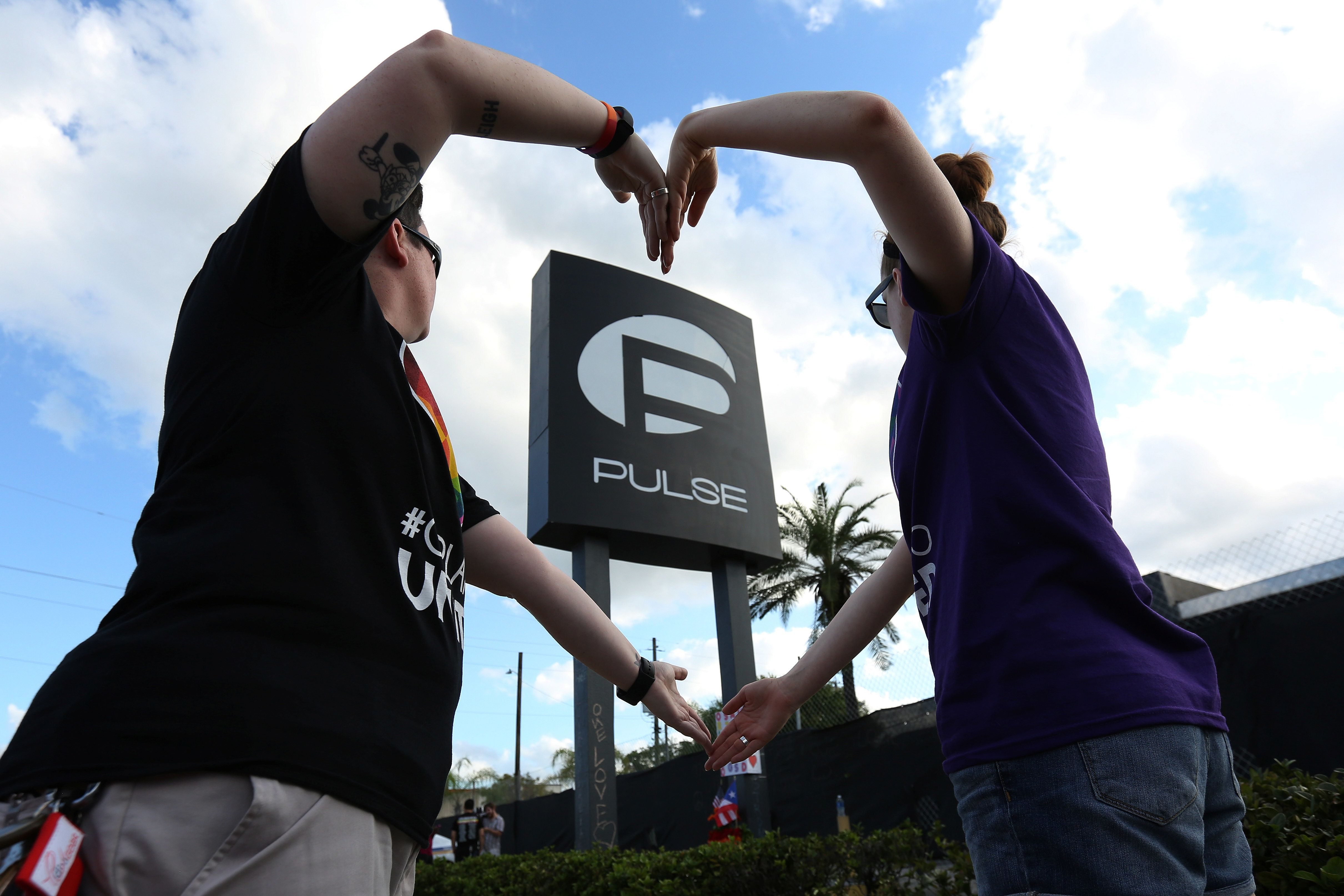 Heather Raleigh (L) and Paige Metelka make a heart shape as they pose during a photo shoot outside Pulse nightclub following the mass shooting last week in Orlando, Florida, U.S., June 21, 2016.  REUTERS/Carlo Allegri