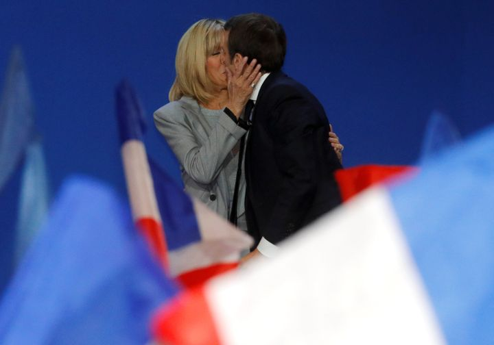 Trogneux kisses Macron before he gives a speech in Paris on April 23, 2017.