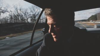 Presidential candidate Bill Clinton rides in a car on his way to a campaign stop in Rhode Island. Clinton would win the 1992 presidential election against incumbent George Bush, and be elected to a second term in 1996. (Photo by mark peterson/Corbis via Getty Images)