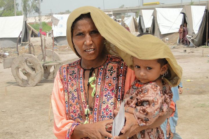 In Pakistan's Sindh province, a mother tries to shield her four-year-old daughter from scorching heat.