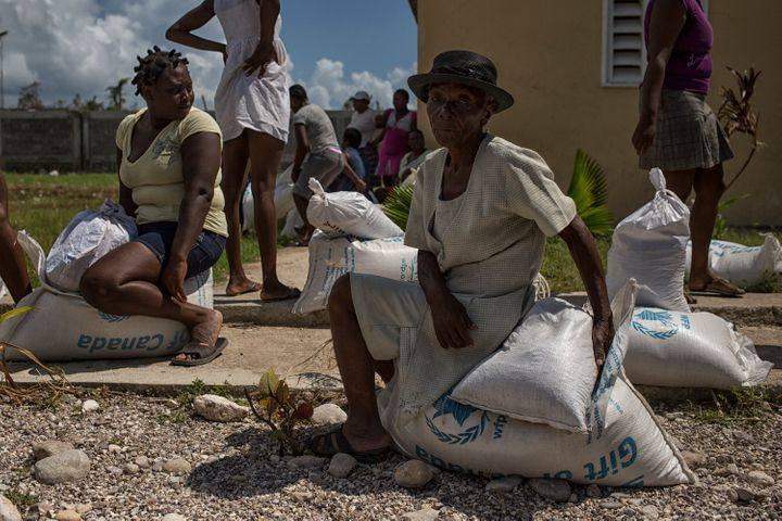 Women in the western Haitian town of Les Cayes collect food and emergency supplies - distributed by the UN, Haitian governmen