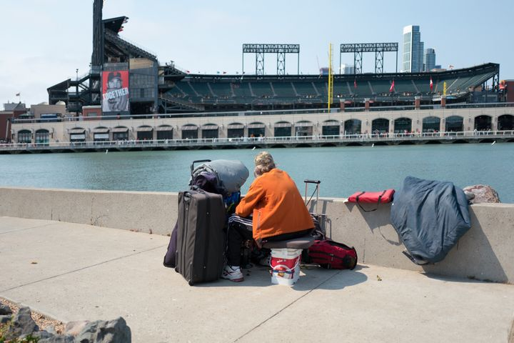 A woman with her belongings looks over at AT&T Park in San Francisco.