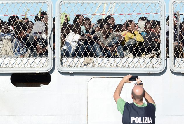 Migrants wait to disembark an Italian Navy ship in the Sicilian harbor of Palermo, southern Italy,...