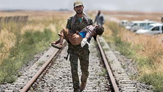 A Kurdish People's Protection Units (YPG) fighter carries a boy injured by what they said was a mine after they fled Maskana town in the Aleppo countryside and make their way towards the Turkish border in Tel Abyad town, Raqqa governorate, June 16, 2015. With a string of victories over Islamic State, Syria's Kurds are proving themselves an ever more dependable ally in the U.S.-led fight against the jihadists and building influence that will make them a force in Middle Eastern politics. Aided by U.S.-led air strikes, the Kurdish-led YPG militia may have dealt Islamic State its worst defeat to date in Syria by seizing the town of Tel Abyad at the Turkish border, cutting a supply route to the jihadists' de facto capital of Raqqa city. REUTERS/Rodi Said