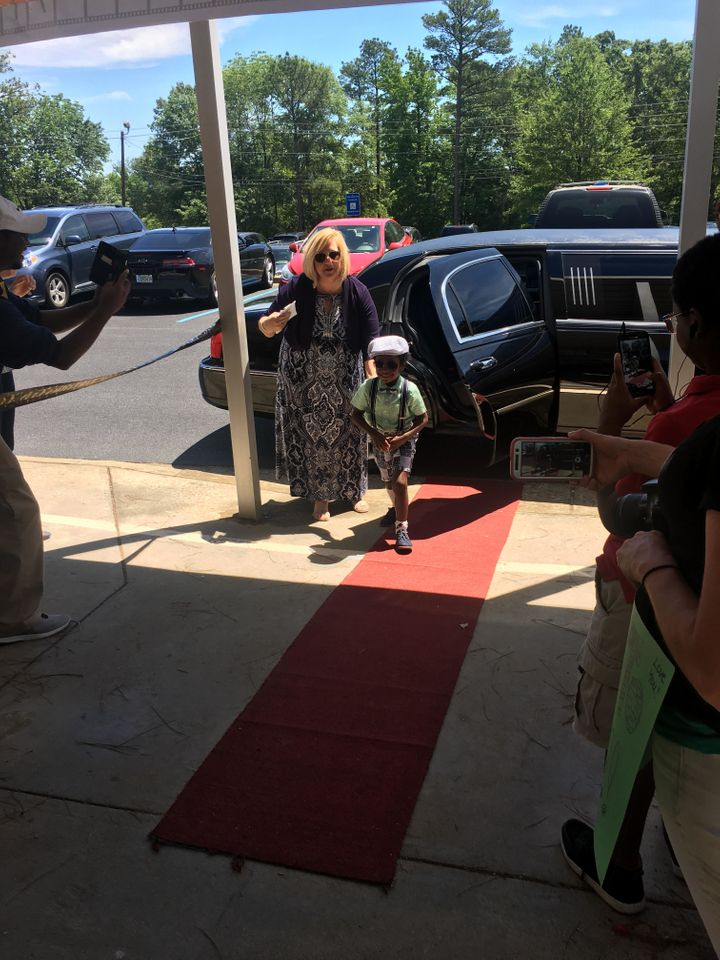 "As the kids step out of the limo onto the red carpet, their teacher announces each ""millionaire."""