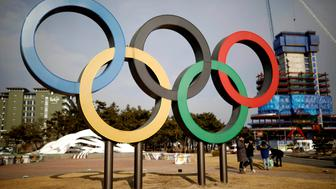 People walk past the Olympic rings in Gangneung, South Korea February 9, 2017. REUTERS/Kim Hong-Ji