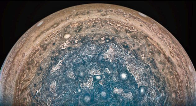 In this enhanced-color view of Jupiter's south pole, photographed by the Juno spacecraft, numerous...