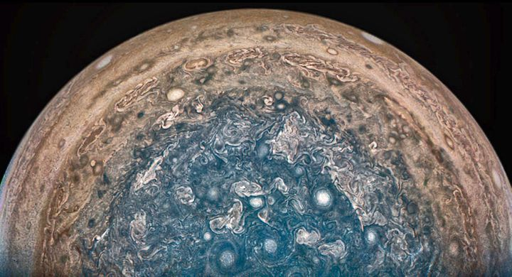 In this enhanced-color view of Jupiter's south pole, photographed by the Juno spacecraft, numerous oval storms -- some as big as Earth -- can be seen among the cloudscape.