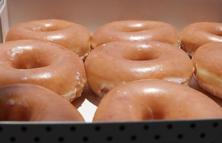 A closeup of a box of Krispy Kreme glazed donuts.