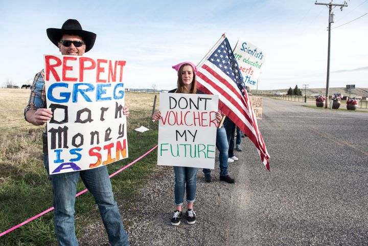 Protestors hold signs at an April rally for Republican Greg Gianforte.