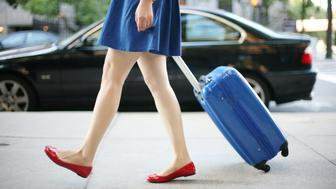 A young lady with a blue skirt and a pair of red flats is walking on the street in the city of Boston. She is pulling a suitcase with the same color of her skirt.