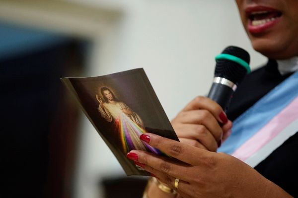 Alexya Salvador, a Brazilian trans pastor, holds a leaflet with an image of Jesus Christ during a mass in a church in Matanza
