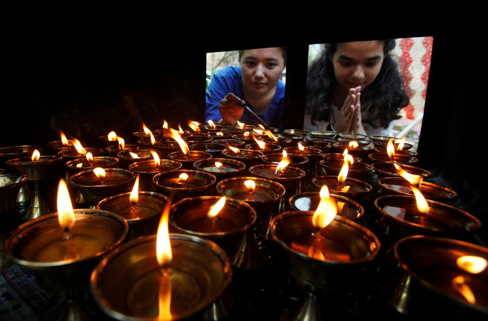 Devotees offer prayers next to oil lamps at a Buddhist temple on the occasion of Buddha Purnima festival, also known as Vesak