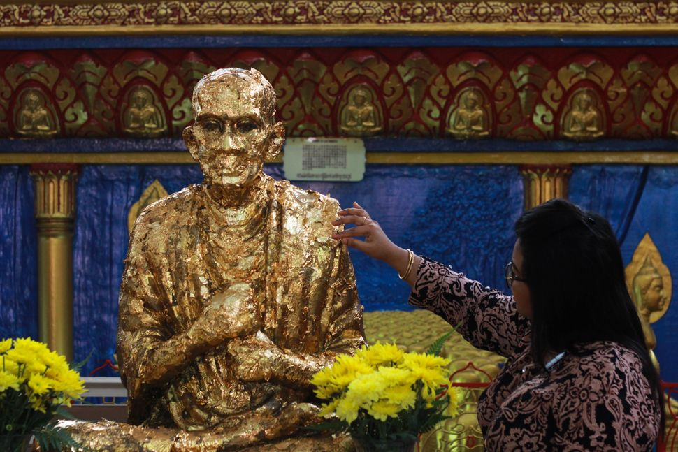 A devotee puts a golden paper onto Buddha statue during Vesak day in Penang, Malaysia, on May 10,2017.