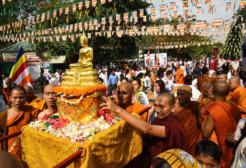 Buddhist Monks carry a statue of Buddha as they take part in a procession at The Mahabodi Temple at Bodhgaya on May 10, 2017,