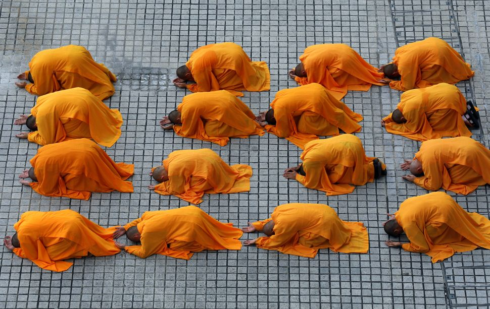 "Buddhist monks prostrate as they perform the ""three steps one bow"" ceremony at Kong Meng San Phor Kark See Monastery on the e"