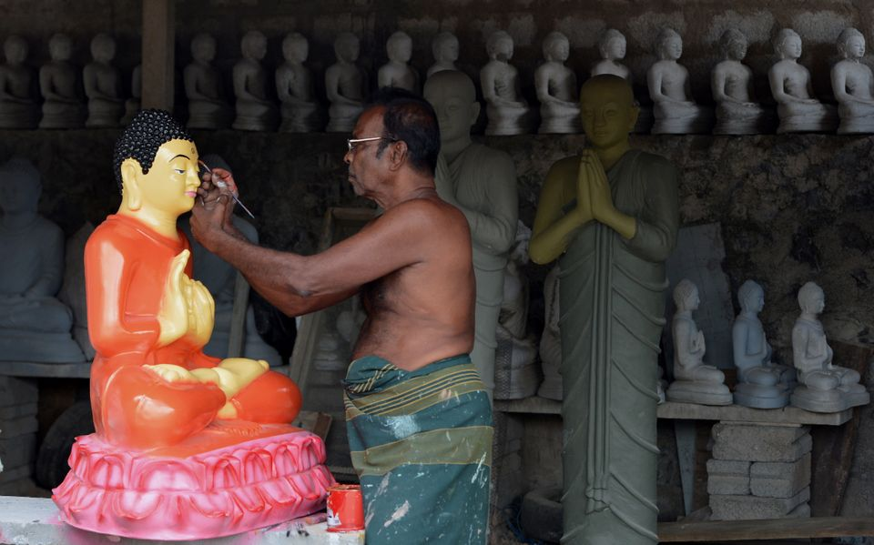 A Sri Lankan artist works on Buddhist statues ahead of the Vesak Festival in Dompe, on the outskirts...