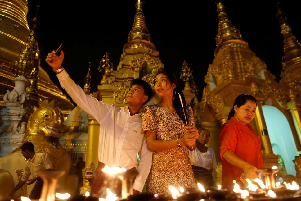 A family takes a seflie as they visit the Shwedagon Pagoda during Kason Watering Festival celebrations, also know as Vesak Da