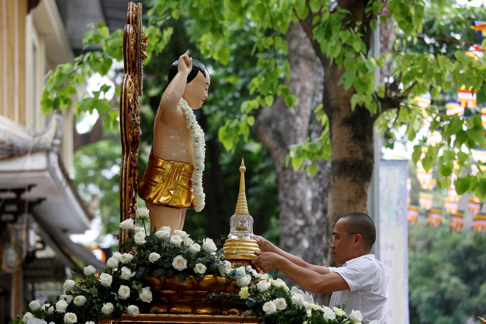 A man places a container holding what is believed to be the relics of Buddha in front of a Child Buddha statue while celebrat