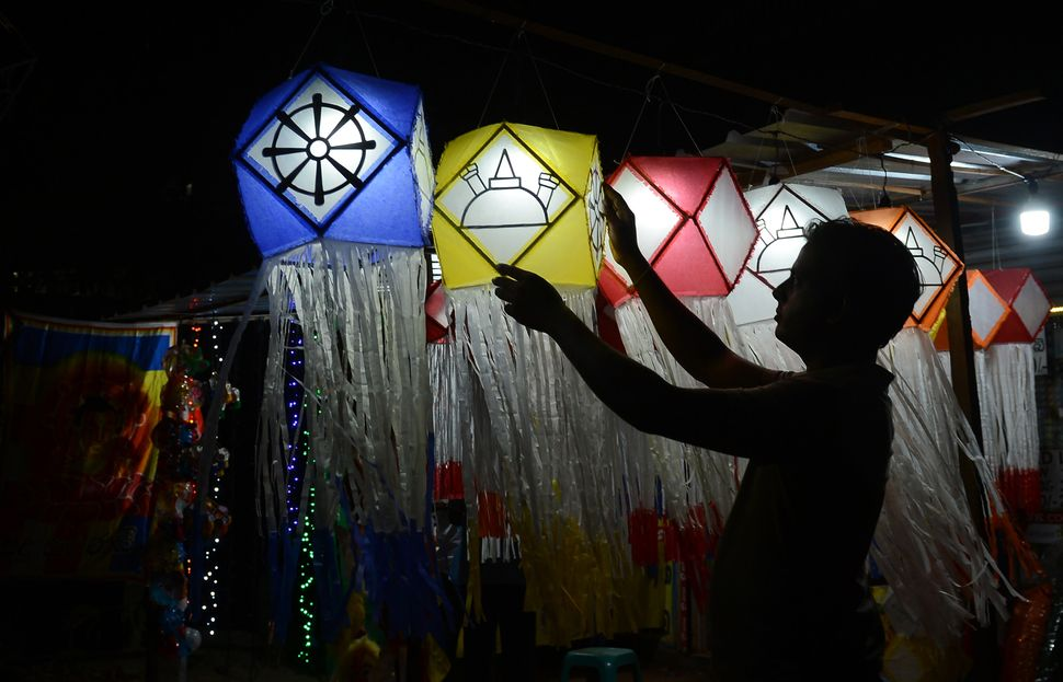 A Sri Lankan street vendor hangs lanterns for sale ahead of the Vesak Festival in Colombo on May 4, 2017.