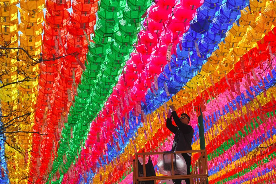 A South Korean worker attaches a name card with a wish of Buddhist followers to a lotus lantern at Jogye Temple in Seoul on A
