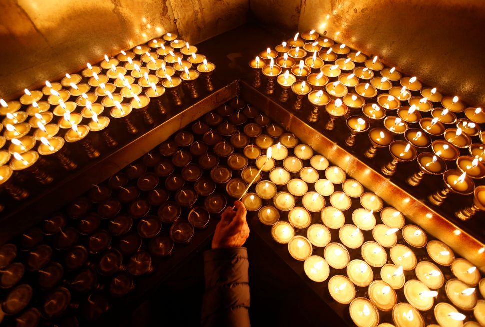 A hand of a devotee is pictured as she offers butter lamps during the birth anniversary of Buddha, also known as Vesak Day, a