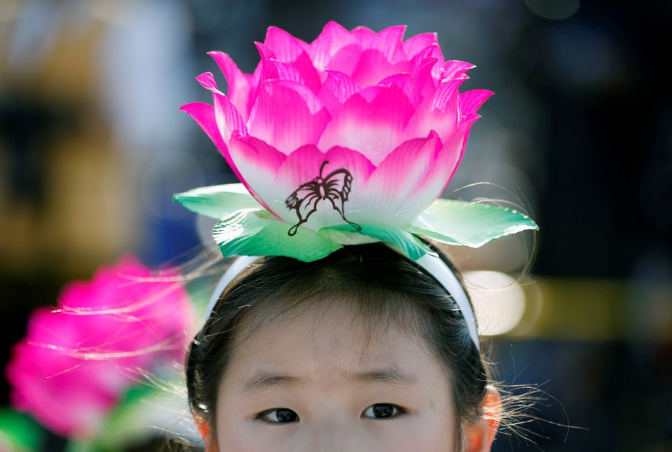 A child wearing a lantern headband rests before a Lotus Lantern parade in celebration of the upcoming birthday of Buddha in S