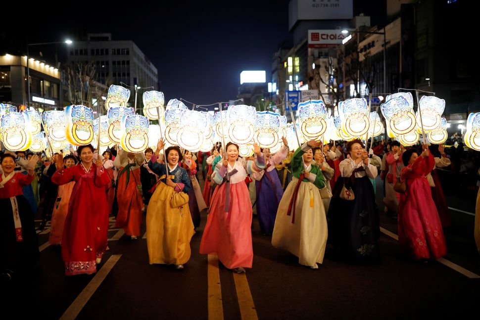 Buddhist believers carrying lanterns march during a Lotus Lantern parade in celebration of the upcoming birthday of Buddha in