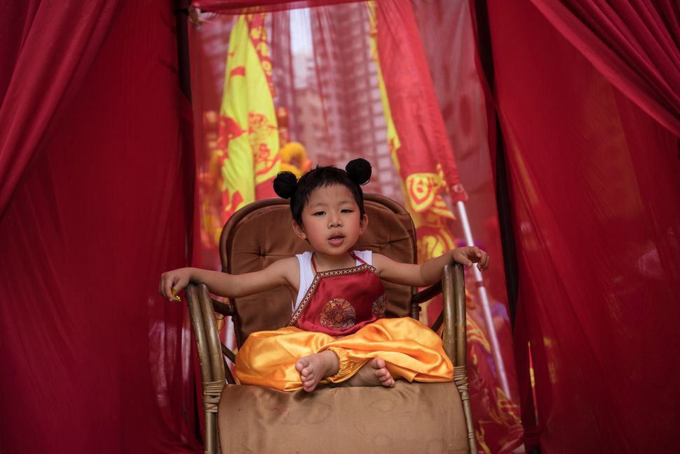 A child sitting on a chair during the Buddha's Birthday festival in Shau Kei Wan, Hong Kong, on May 3, 2017.