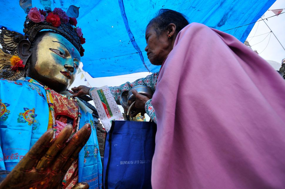 Nepalese devotee offers ritual prayer towards a Buddha at the Chiloncho Stupa during the celebration of Buddha Purnima f