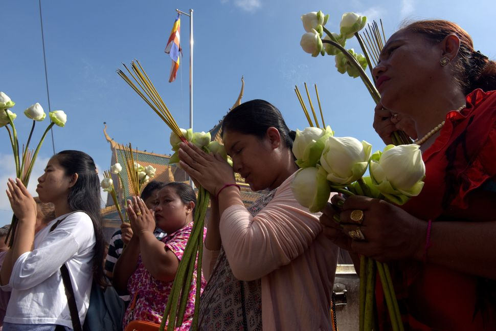 Cambodian women pray in front of a shrine out side the Royal Palace in Phnom Penh on May 10, 2017. Cambodians celebrated 2,56