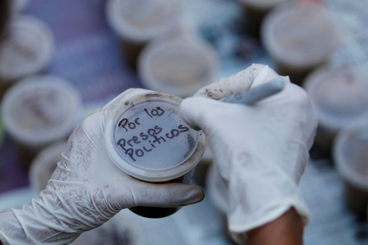 "A woman writes a text that reads ""For the political prisoners"" on a plastic pot filled with feces."