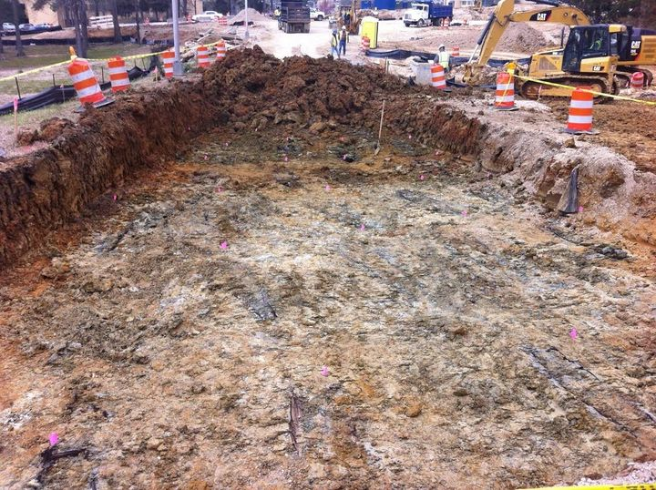 Outlines of wooden coffins found during excavations at the University of Mississippi Medical Center's campus are seen. Each grave is marked with a pink flag.